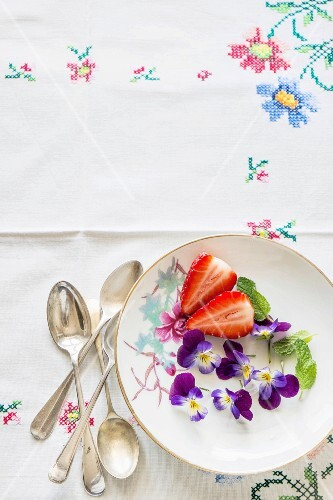 Fresh strawberries, violets and mint on a plate