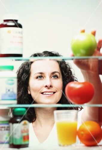 A woman choosing between vitamin tablets and fresh fruit and vegetables
