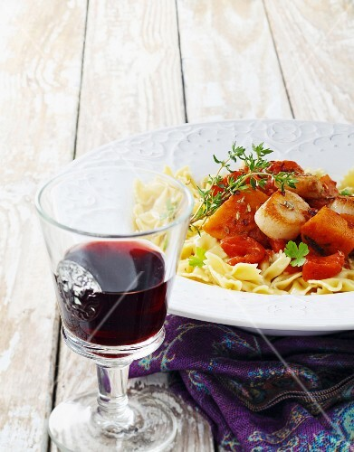 Pasta with scallops and tomatoes and a glass of red wine