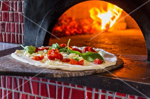Margherita pizza with Piennolo tomatoes being placed in an oven