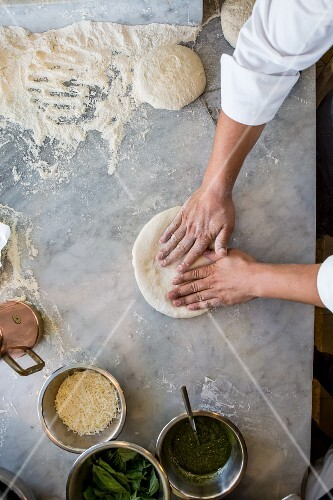 A pizza being made (dough being pressed flat)