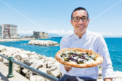 Gino Sorbillo, a pizza baker from Naples, holding a pizza