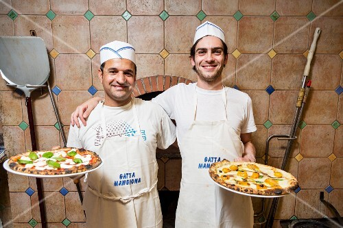 Pizza bakers in front of the oven in the Pizzeria La Gatta Mangiona in Rome, Italy