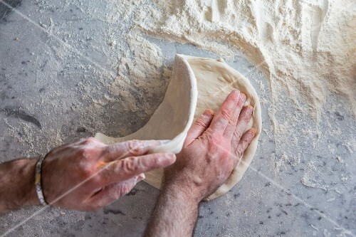 Pizza dough being rolled out