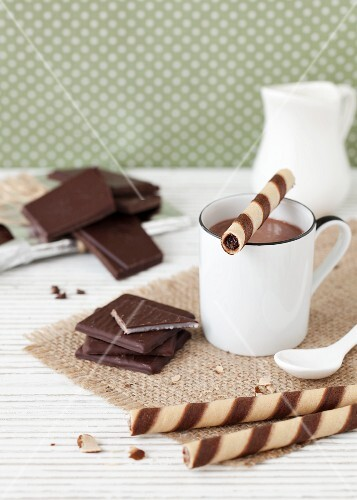 A cup of hot chocolate served with after dinner mints and wafer cigars