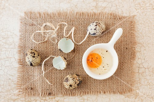 Three whole quail's eggs with a cracked open egg and shells