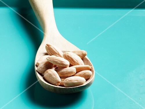 Shelled almonds on wooden spoon