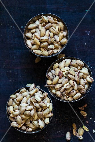 Three bowls of unshelled pistachio nuts (seen from above)