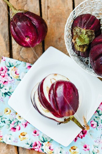Fresh aubergines on a wooden table with floral-patterned napkins