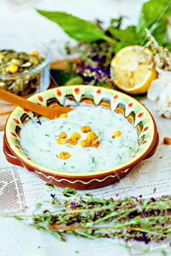 Traditional Bulgarian Tarator soup with herbs, lemons and salted corn