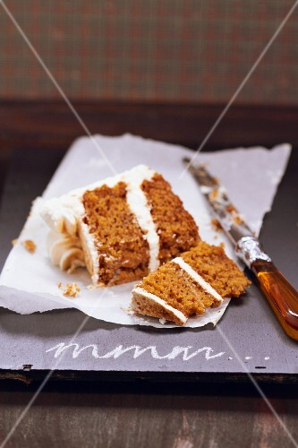 A slice of carrot cake with cream cheese frosting, cut in two pieces