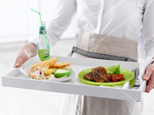 A woman carrying two different dishes on a white tray