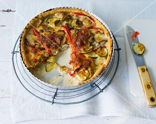 A colourful vegetable quiche with red peppers, courgettes and mushrooms