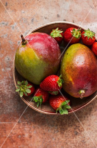A bowl of mangos and strawberries