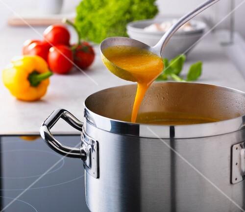 Pumpkin soup in a pot with a ladle