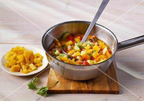 Bean soup with colourful vegetables and crispy potatoes