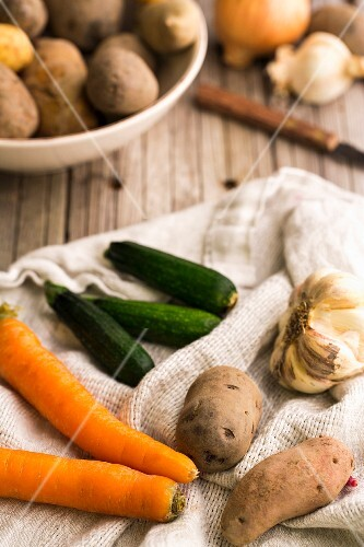 An arrangement of vegetables featuring carrots, potatoes, garlic and courgettes on a tea towel