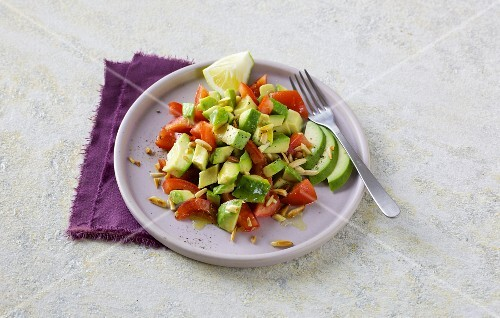 Avocado with tomatoes, almonds and pine nuts