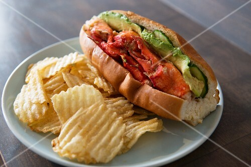 Grilled lobster rolls with avocado and pickles served with ridged potato crisps