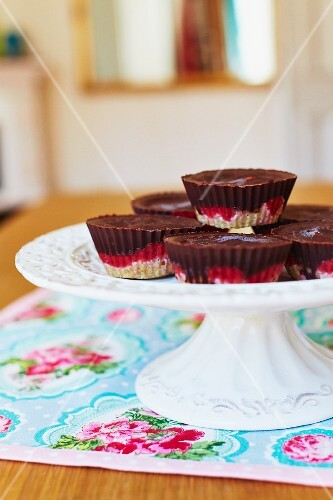 Layered detox cupcakes with cashew nut bases, a strawberry and apricot filling and topped with argave syrup and cocoa powder