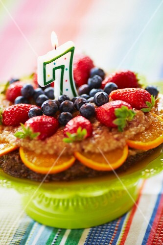 Detox cake with a banana and apple topping, fresh berries and oranges and nut-free base made from carob powder, dried fruits and coconut flakes