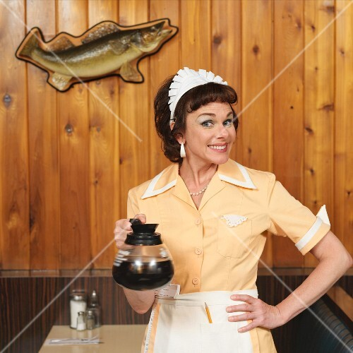 A waitress in a diner holding a pot of coffee