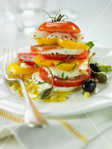 A stack of sliced tomatoes, peppers and mozzarella with olives and capers