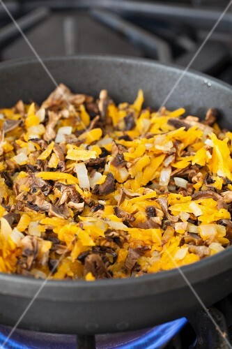 Carrots, onions and soaked mushrooms in a pan for buckwheat hash