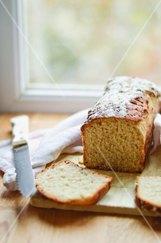 Bread and a knife on a wooden board in front of a kitchen window