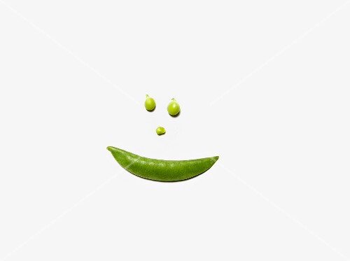 A smiley face made from a pea pod and peas