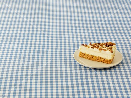 A slice of cheesecake with walnuts and maple syrup