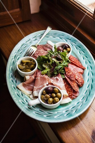A meat platter with bacon, olives and gherkins