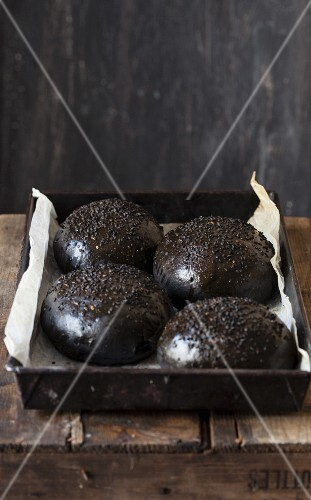 Black brioche rolls on a baking tray