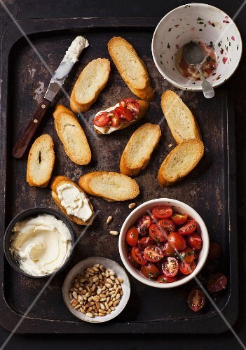Ingredients for bruschetta with tomatoes, whipped goat cheese and pine nuts