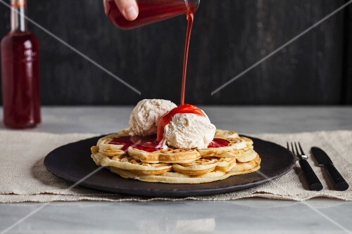 Strawberry syrup being poured on waffles with vanilla ice cream