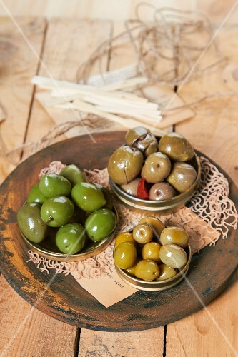 Various marinated, green olives in three metal lids