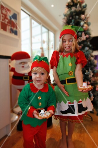 Two children holding homemade Christmas biscuits