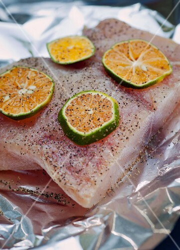 Raw golden mackerel fillet with pepper and orange slices on a piece of aluminium foil