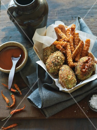 Crab cakes with sweet potato fries in a wooden basket with a dip