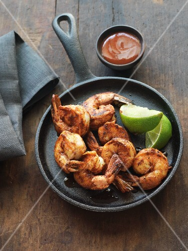 Blackened shrimps in a pan with lime wedges