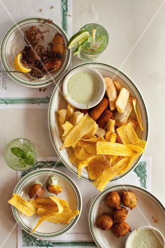 A platter of fried, sweet plantains, dill mayonnaise, empanadas and fried yuca sticks with pork with rice and beans, fish croquettes and mojitos