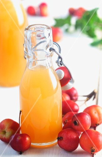 Fresh apple juice in a flip-top bottle decorated with ornamental apples