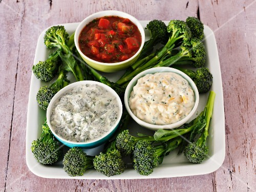 Various dips (salsa, raita, and a cheese and chive dip) with broccoli