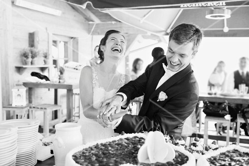 A bride and bridegroom cutting their wedding cake