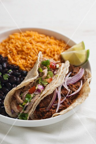 Tacos with various meat fillings, black beans and tomato rice
