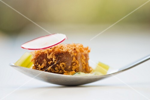 A piece of roasted beef fillet with crispy breadcrumbs on a spoon