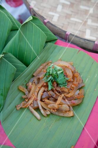 Spicy pork rind salad on a banana leaf (Thailand)