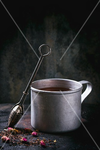 Tea in a tin mug with a tea strainer and dried rose buds on a black metal surface