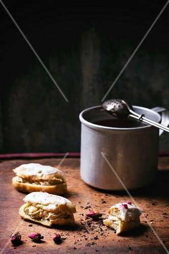 Mini eclairs, whole and half-eaten, next to a cup of tea on a wooden table