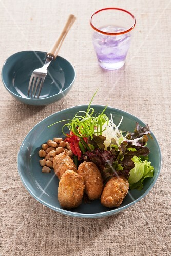 Rice croquettes with a side salad and peanuts